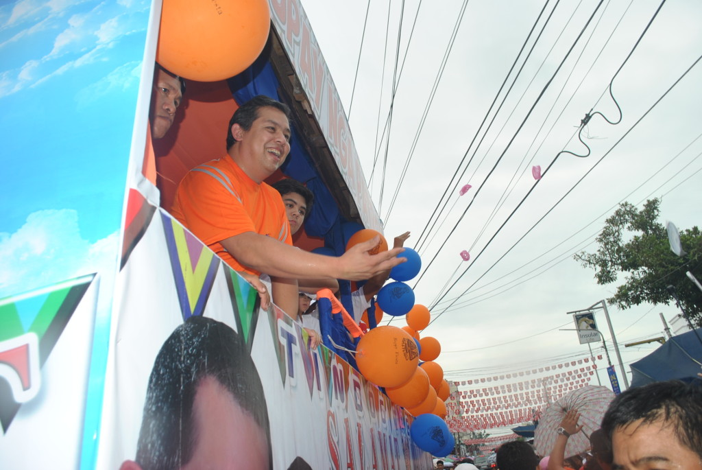 """Leyte Representative Ferdinand Martin """"FM"""" Romualdez good naturedly throws apples and some goodies to the throng of people who watched the Sangyaw Festival on June 29 in the streets of Tacloban. Tacloban marked its 125th annual fiesta on June 30 this year.(LITO A. BAGUNAS)"""